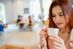 Mujer hermosa y sostener una taza de café en su mano en cafetería del fondo de la falta de definición Foto de archivo