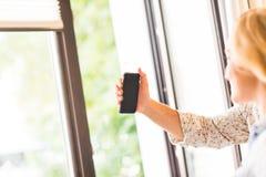 Mujer hermosa y su amigo que hacen un selfie usando el teléfono elegante Fotos de archivo libres de regalías