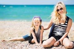 Mujer hermosa y su hija encantadora que descansan sobre la playa Imagen de archivo