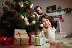 Mujer hermosa y su hija que descansan bajo tre de la Navidad imagenes de archivo