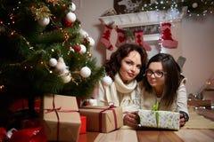 Mujer hermosa y su hija que descansan bajo tre de la Navidad fotos de archivo libres de regalías