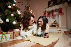 Mujer hermosa y su hija que descansan bajo tre de la Navidad fotografía de archivo libre de regalías