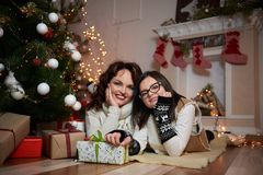 Mujer hermosa y su hija que descansan bajo tre de la Navidad foto de archivo