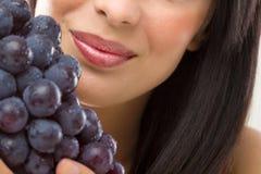 Mujer hermosa y uvas frescas Imagenes de archivo
