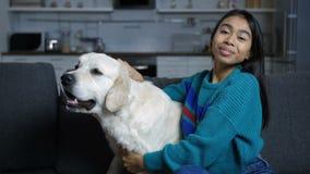 Mujer hindú joven que acaricia y que abraza el perro en el sofá metrajes