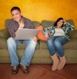 Mujer hispánica aburrida que reacciona al hombre con el ordenador Fotos de archivo