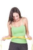 Mujer hispánica de la pérdida de peso que sonríe con la medición Foto de archivo libre de regalías