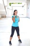 mujer hispánica deportiva en bíceps azul del entrenamiento con pesa de gimnasia azul al aire libre Imágenes de archivo libres de regalías