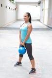 Mujer hispánica deportiva en el azul que levanta el kettlebell azul para la elevación muerta, al aire libre Imagenes de archivo
