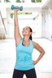 mujer hispánica deportiva en la elevación azul con la mano derecha, una pesa de gimnasia azul al aire libre Imagenes de archivo