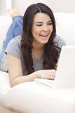 Mujer hispánica feliz que usa el ordenador portátil Foto de archivo libre de regalías