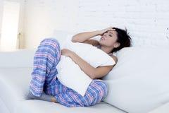 Mujer hispánica hermosa en la expresión dolorosa que sostiene el vientre que sufre dolor del período menstrual Fotos de archivo libres de regalías