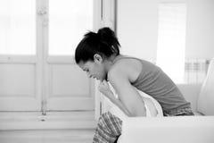 Mujer hispánica hermosa en la expresión dolorosa que sostiene el vientre que sufre dolor del período menstrual Foto de archivo