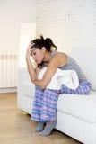 Mujer hispánica hermosa en la expresión dolorosa que sostiene el vientre que sufre dolor del período menstrual Imagen de archivo