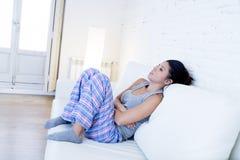 Mujer hispánica hermosa en la expresión dolorosa que sostiene el vientre que sufre dolor del período menstrual Imágenes de archivo libres de regalías