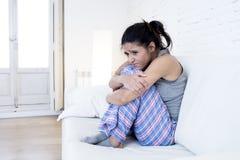 Mujer hispánica hermosa en la expresión dolorosa que sostiene el vientre que sufre dolor del período menstrual Fotos de archivo