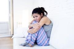 Mujer hispánica hermosa en la expresión dolorosa que sostiene el vientre que sufre dolor del período menstrual Imagenes de archivo