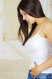Mujer hispánica hermosa joven en la expresión dolorosa que toca su vientre, dolor sufridor del período menstrual, salud femenina Imagen de archivo