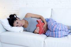 Mujer hispánica hermosa joven que sostiene la botella de agua caliente contra el vientre que sufre dolor del período menstrual Fotografía de archivo