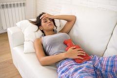 Mujer hispánica hermosa joven que sostiene la botella de agua caliente contra el vientre que sufre dolor del período menstrual Foto de archivo libre de regalías