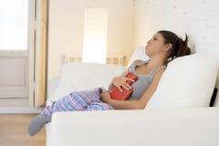Mujer hispánica hermosa joven que sostiene la botella de agua caliente contra el vientre que sufre dolor del período menstrual Fotografía de archivo libre de regalías
