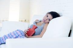 Mujer hispánica hermosa joven que sostiene la botella de agua caliente contra el vientre que sufre dolor del período menstrual Imagen de archivo