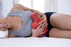 Mujer hispánica hermosa joven que sostiene la botella de agua caliente contra el vientre que sufre dolor del período menstrual Foto de archivo