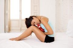 Mujer hispánica hermosa joven que sostiene la botella de agua caliente contra el vientre que sufre dolor del período menstrual Fotos de archivo