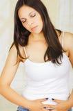Mujer hispánica hermosa joven que toca su vientre con ambas manos, dolor sufridor del período menstrual, salud femenina Foto de archivo