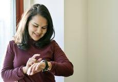 Mujer hispánica hermosa que usa el reloj elegante Foto de archivo libre de regalías