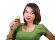 Mujer hispánica hermosa y feliz joven que come la magdalena azucarada amarilla sabrosa y deliciosa que presenta en fondo aislado  fotografía de archivo