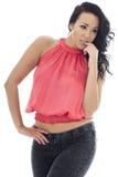 Mujer hispánica joven atractiva con la expresión preocupante que lleva un top rosado y vaqueros negros Foto de archivo libre de regalías