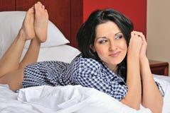 Mujer hispánica joven atractiva en cama en la camisa de los hombres Imágenes de archivo libres de regalías