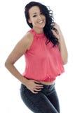 Mujer hispánica joven atractiva que presenta en un top rosado y vaqueros negros Fotografía de archivo libre de regalías