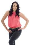 Mujer hispánica joven atractiva que presenta en un top rosado y vaqueros negros Fotos de archivo