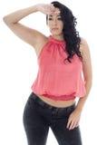 Mujer hispánica joven atractiva que presenta en un top rosado y vaqueros negros Foto de archivo libre de regalías