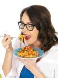 Mujer hispánica joven feliz hermosa que come una placa del tomate y de Basil Fusilli Pasta Imágenes de archivo libres de regalías