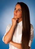 Mujer hispánica joven pensativa que piensa delante de backgroun azul Imagen de archivo libre de regalías