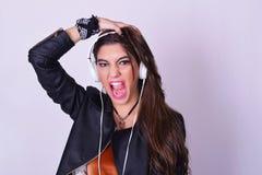 Mujer hispánica joven que escucha la música con los auriculares Fotos de archivo libres de regalías