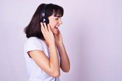 Mujer hispánica joven que escucha la música con los auriculares fotografía de archivo libre de regalías