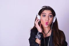 Mujer hispánica joven que escucha la música con los auriculares Foto de archivo libre de regalías