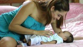 Mujer hispánica joven que juega con su pequeño bebé en cama almacen de video