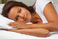 Mujer hispánica joven que miente en una cama Imagen de archivo