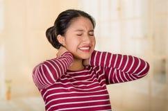 Mujer hispánica joven que presenta para la cámara que muestra las muestras del dolor de cuello, llevando a cabo las manos en la p Fotografía de archivo