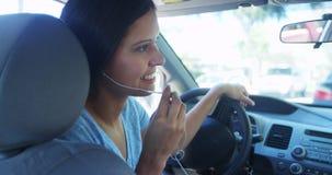 Mujer hispánica que habla en el coche con los auriculares Imagen de archivo libre de regalías