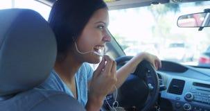 Mujer hispánica que habla en el coche con los auriculares Imágenes de archivo libres de regalías