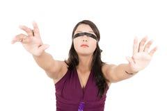 Mujer hispánica que la cubre ojos con una venda Imagen de archivo
