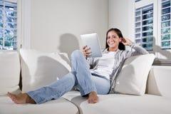 Mujer hispánica que lee el libro electrónico en el sofá Fotos de archivo libres de regalías