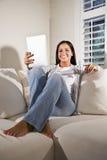 Mujer hispánica que lee el libro electrónico en el sofá Foto de archivo libre de regalías