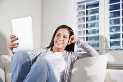 Mujer hispánica que lee el libro electrónico en el sofá Imágenes de archivo libres de regalías